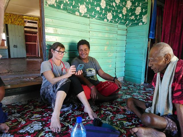 Suanne in the fiji village showing the phone pictures - Hospital Internship & Health Program Review