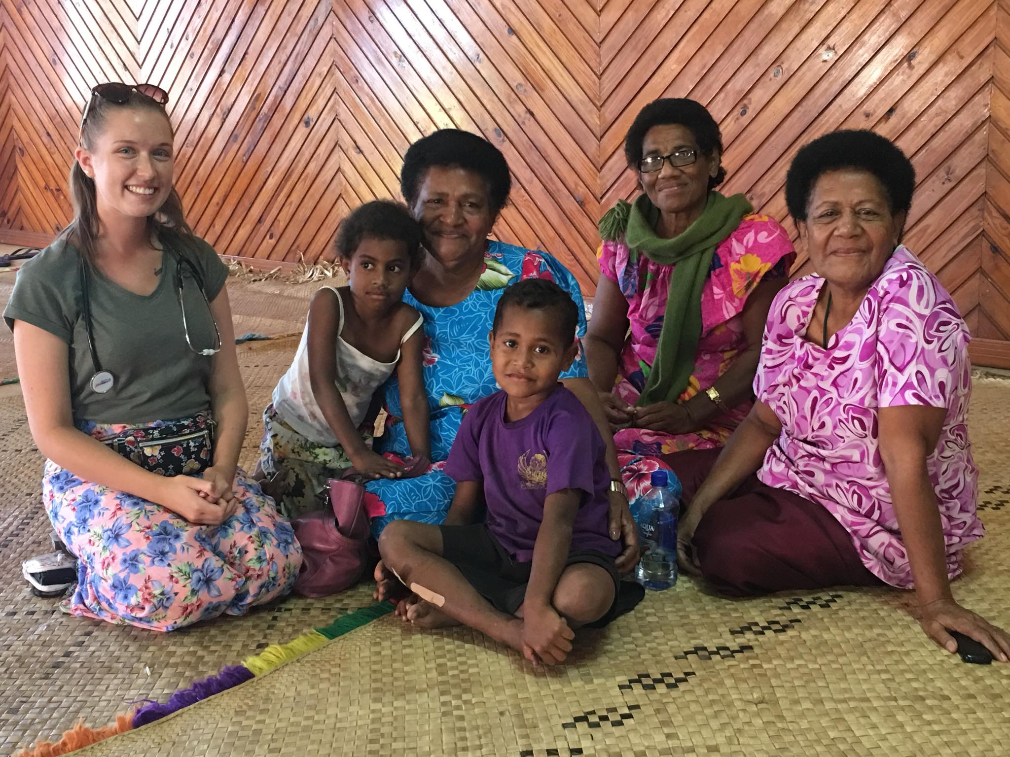 lovely shot with volunteer health worker and fijian woman and children - IVI Doing Health Checks in 5* Fiji Resorts