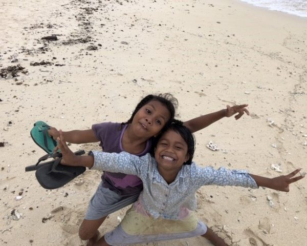 children smiling on beach in fiji remote island