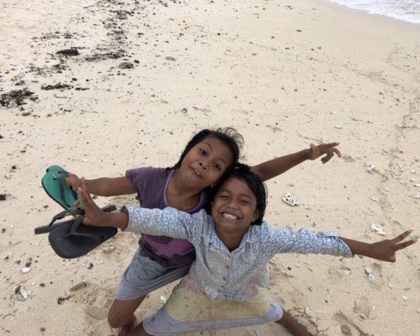 children smiling on beach in fiji remote island