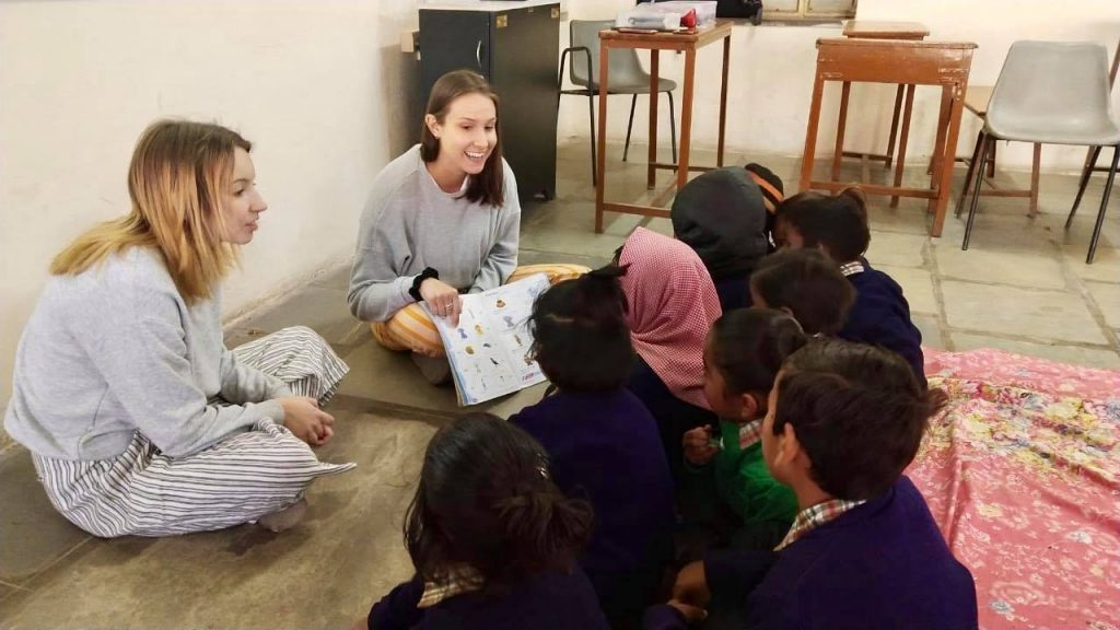 volunteers reading books to children in nepal