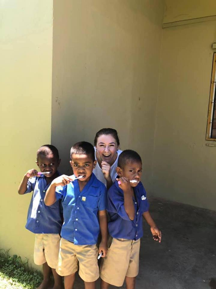 Stephanie Bell with fijian childen brushing teeth - About IVI's Health Check Work with Fiji Housing Developments
