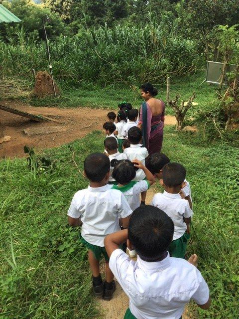 sri lanka children standing in line in green grass e1565336441592 - Childcare and Construction Volunteering Sri Lanka
