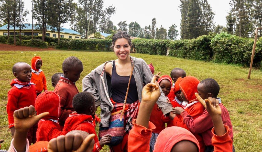 Students gathered around participant - Meet Your Hosts in Kenya