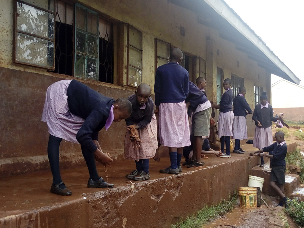 Kenyan children cleaning outside thier classroom-2