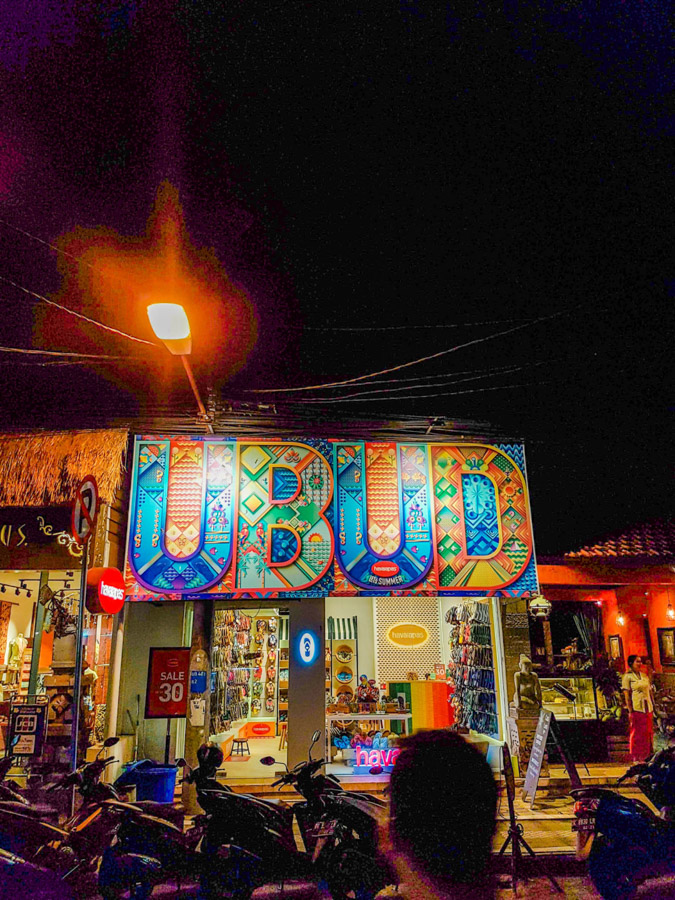 'Ubud' shop sign in street at night