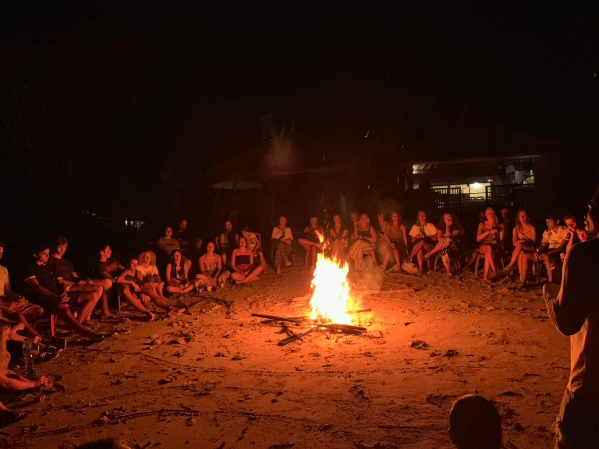 big group sitting around a bonfire