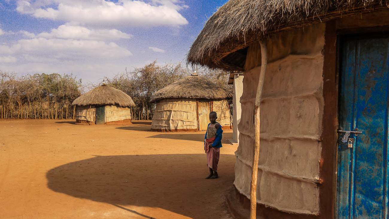 child by mud huts in Tanzania