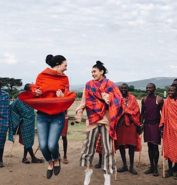 girls jumping with group of Maasai men