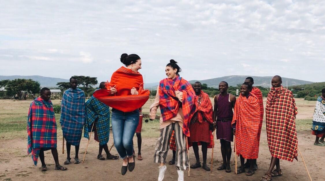 girls jumping with group of Maasai men