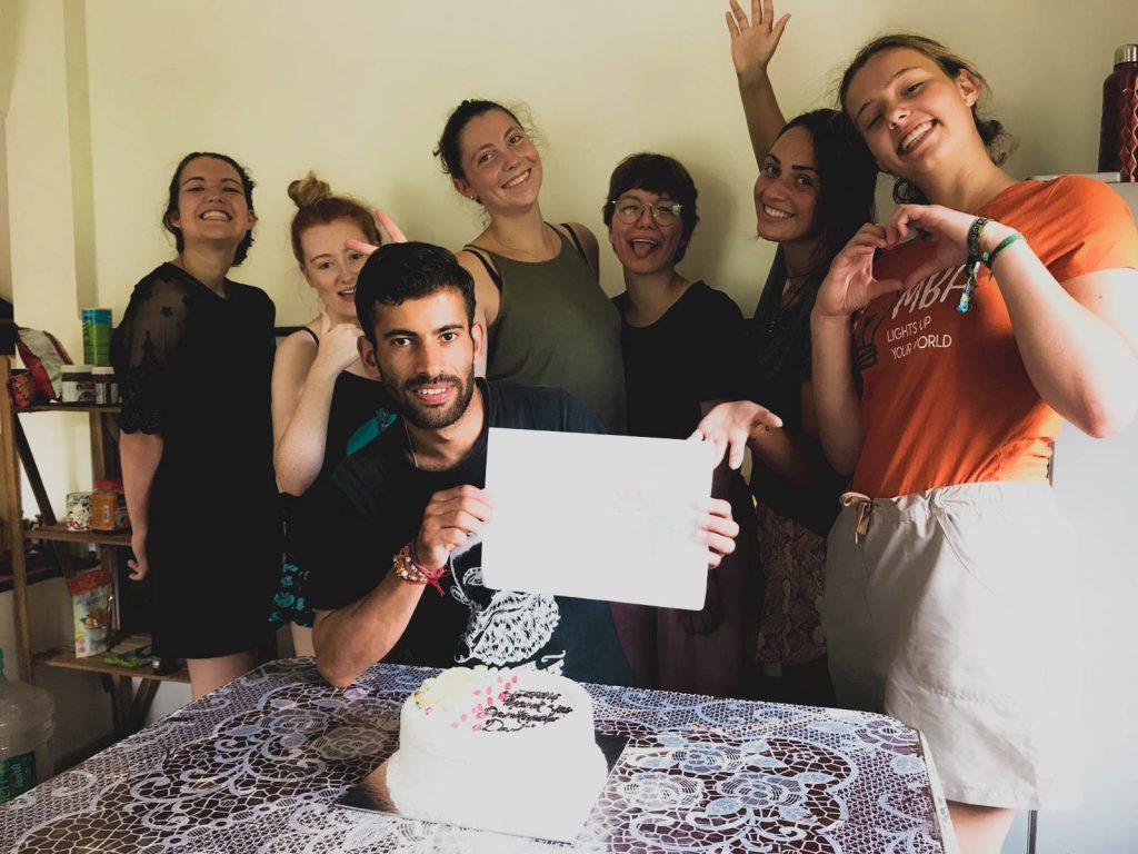 group standing around birthday cake