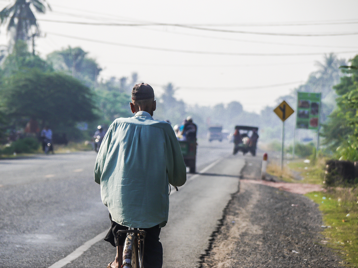 man riding bike alongside road