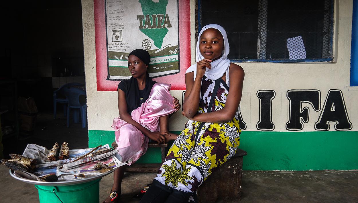 young Kenyan women sittng outside shop