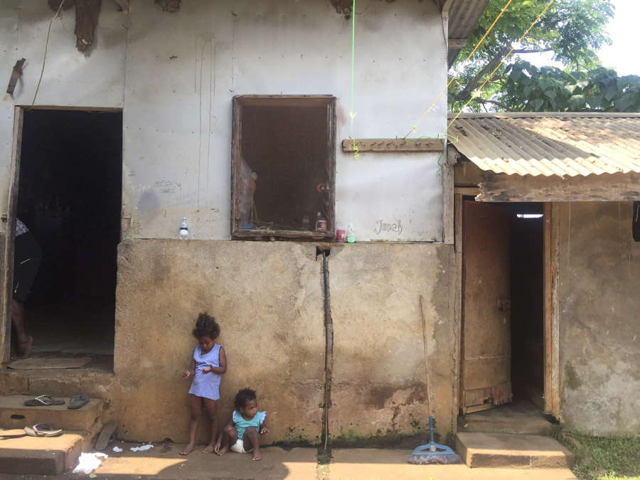 2 kids sitting outside home in Vanuatu