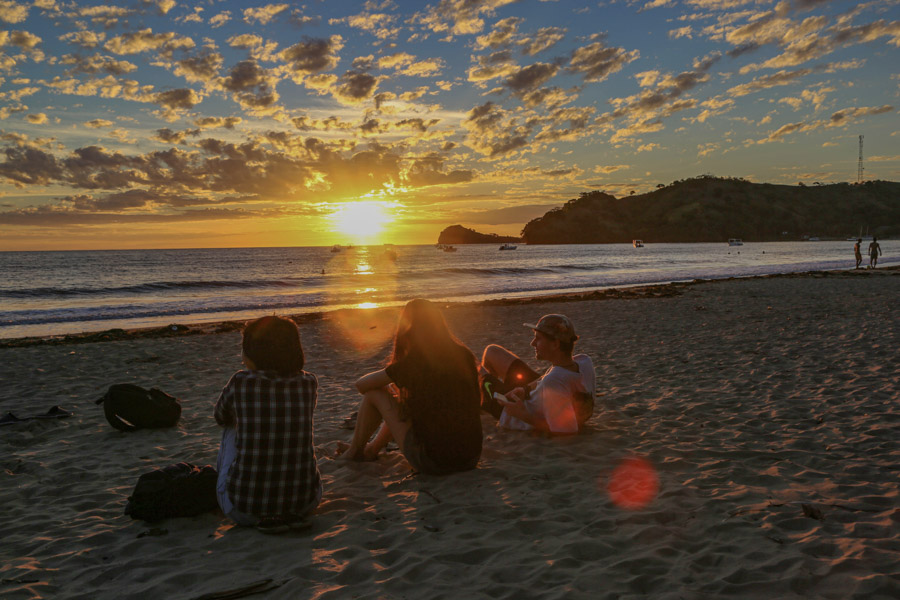 group sitting on the beach at sunset