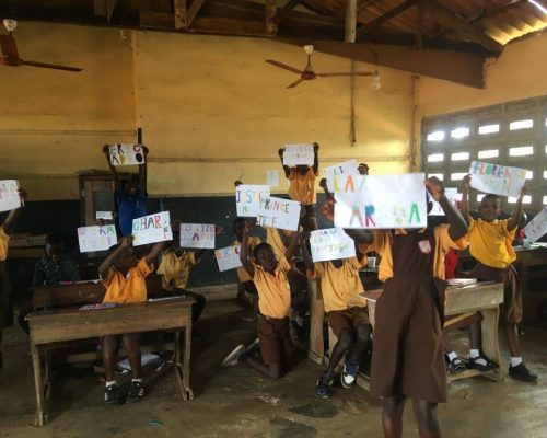 children holding up their art work
