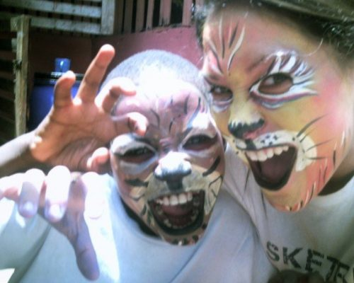 volunteer and child with face paint