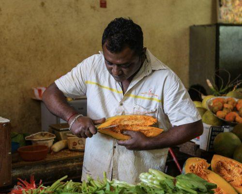man cutting fruit