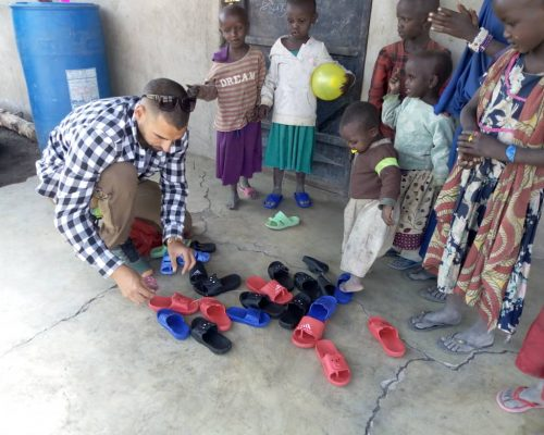 volunter giving new shoes to children on teaching project