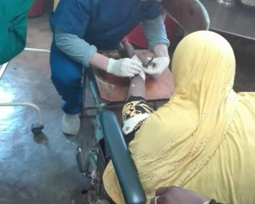 volunteer treating a wound on medical project, Tanzania