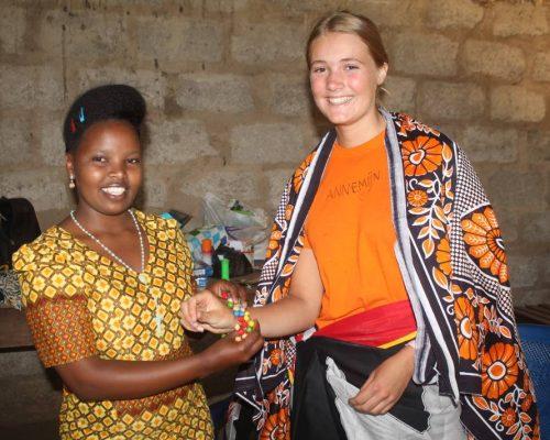 Tanzanian teacher giving gift to volunteer
