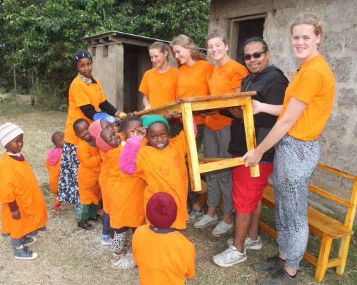 volunteers with students, helping to carry classroom desk