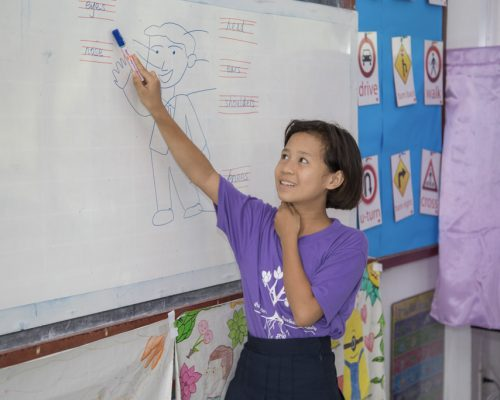 Student filling out activity on white board