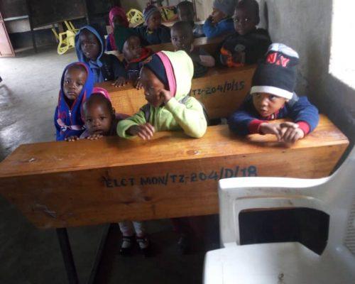 Tanzanian children sitting on school desks