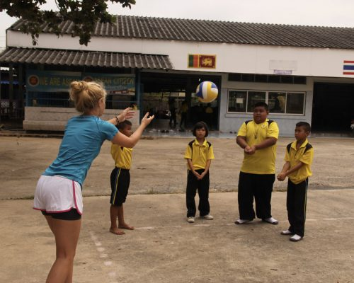 Students playing volleyball with participants