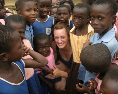 volunteer surrounded by children in Ghana