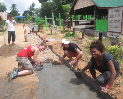 volunteers laying the path outside rural school cambodia