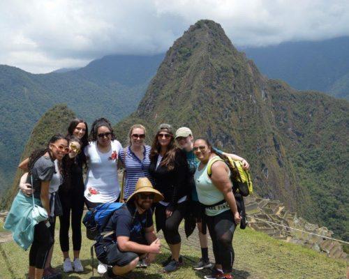 Cusco volunteers in front of machu pichu amazing scenery