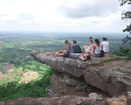 5 volunteers on the cliff looking out to distant cambodia