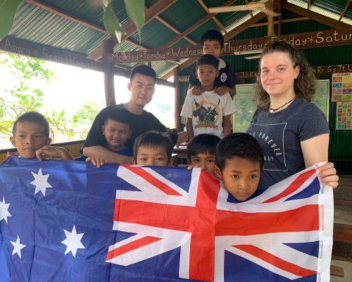joydyn with kids in cambodia and australia flag