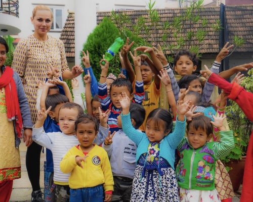 kindergarten children with hands in air