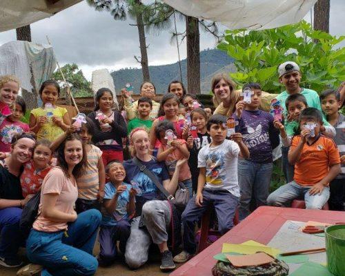 children holding up art work