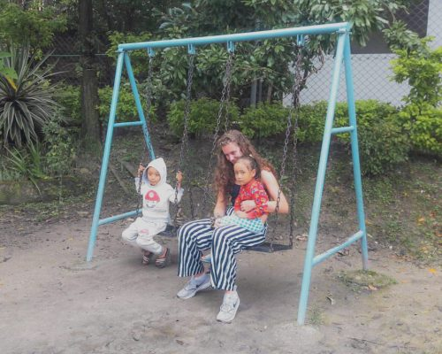playing on swings with Nepalese kids