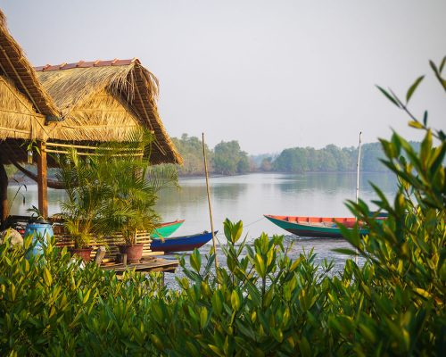 straw huts by river in Cambodia